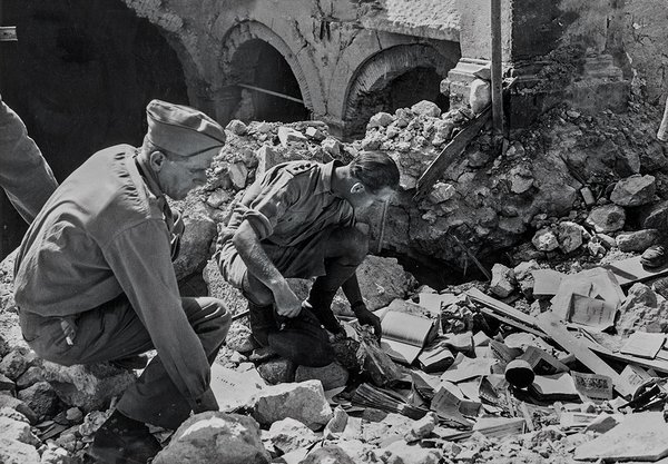 Monuments Officers Ernest De Wald and Roger Ellis sift through the rubble of the Abbey of Monte Cassino destroyed by Allied bombing in 1944.